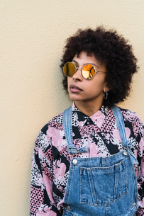 Cool young woman in dungarees and sunglasses standing in front of wall, portraitの写真素材 [FYI03621975]