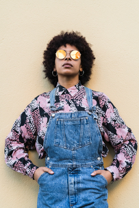 Cool young woman in dungarees and sunglasses standing in front of wall, portraitの写真素材 [FYI03621976]