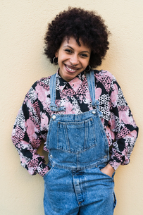 Young woman in dungarees standing in front of wall, portraitの写真素材 [FYI03621978]
