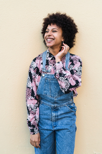 Happy young woman in dungarees standing in front of wall, portraitの写真素材 [FYI03621979]