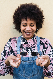 Young woman in dungarees holding sunglasses, portraitの写真素材 [FYI03622005]