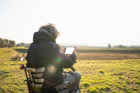 Man on wheels using digital tablet in countrysideの写真素材 [FYI03622014]