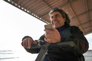 Man on wheels with smartphone enjoying seasideの写真素材 [FYI03622024]