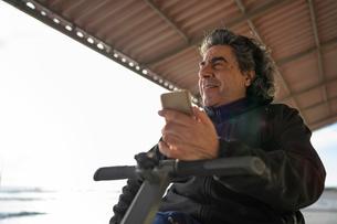 Man on wheels with smartphone enjoying seasideの写真素材 [FYI03622027]