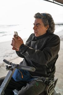Man on wheels using smartphone at seasideの写真素材 [FYI03622029]