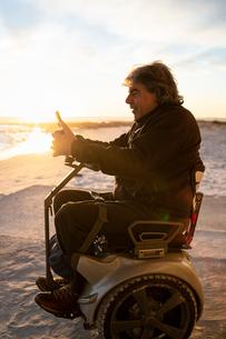 Man on wheels using smartphone at seasideの写真素材 [FYI03622031]