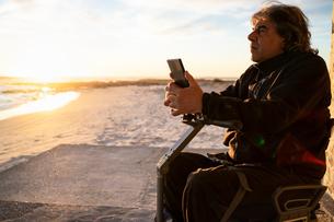 Man on wheels with smartphone enjoying seasideの写真素材 [FYI03622032]