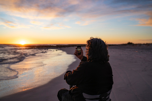 Man on wheels taking photograph of sunset with smartphone at seasideの写真素材 [FYI03622037]