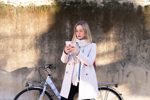 Female higher education student with bicycle looking at smartphoneの写真素材 [FYI03622045]