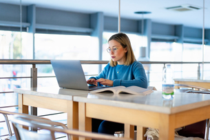 Female higher education student using laptop in university cafeの写真素材 [FYI03622048]
