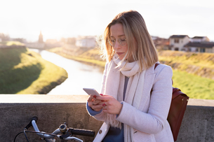Female higher education student on river bridge looking at smartphone, Florence, Italyの写真素材 [FYI03622049]