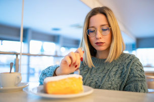 Female higher education student eating cake in university cafeの写真素材 [FYI03622065]