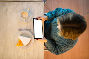 Female higher education student looking at digital tablet in university cafe, overhead viewの写真素材 [FYI03622067]