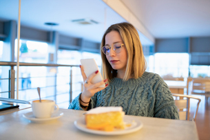 Female higher education student looking at smartphone in university cafeの写真素材 [FYI03622071]