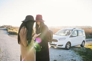 Friends using smartphone on roadsideの写真素材 [FYI03622109]