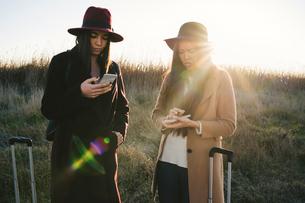 Friends using smartphone on roadsideの写真素材 [FYI03622112]