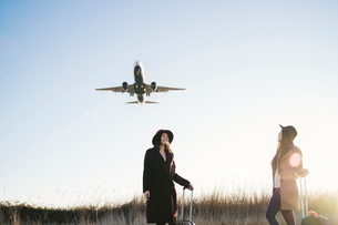 Friends waiting with wheeled luggage on roadside, airplane flying aboveの写真素材 [FYI03622114]