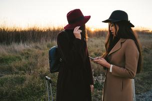 Friends using smartphone on roadsideの写真素材 [FYI03622117]