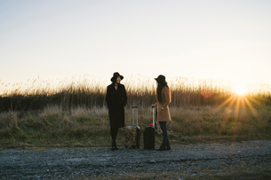 Friends waiting with wheeled luggage on roadsideの写真素材 [FYI03622118]