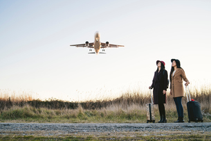 Friends waiting with wheeled luggage on roadside, airplane flying aboveの写真素材 [FYI03622120]