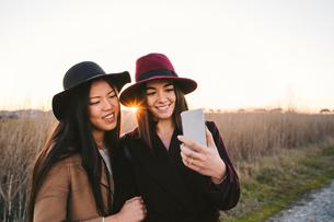 Friends taking selfie on roadsideの写真素材 [FYI03622123]