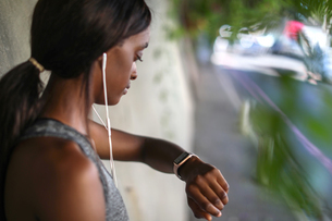 Young female runner listening to earphones and looking at smartwatch on city sidewalkの写真素材 [FYI03622140]
