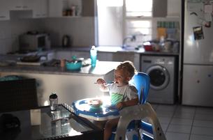 Baby boy feeding himself on high chairの写真素材 [FYI03622200]