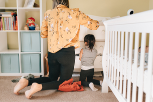 Girl and mother looking through chest of drawers in nursery, rear viewの写真素材 [FYI03622251]