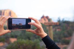 Woman taking photograph of landscapes, Sedona, Arizona, USAの写真素材 [FYI03622385]