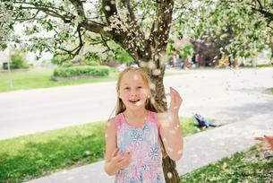 Girl throwing blossom on suburban street, portraitの写真素材 [FYI03622412]