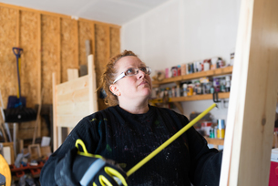 Mature female carpenter looking up at wood planks in workshopの写真素材 [FYI03622436]