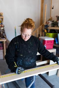 Mature female carpenter measuring wood planks in workshopの写真素材 [FYI03622437]