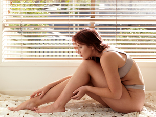 Beautiful curvaceous young woman wearing bra and knickers sitting up on bed touching ankleの写真素材 [FYI03622438]