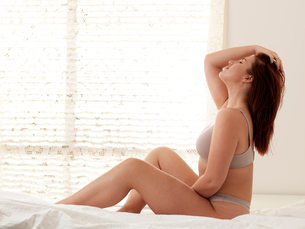 Beautiful curvaceous young woman wearing bra and knickers sitting up on bed with eyes closed and hanの写真素材 [FYI03622440]
