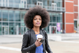 Young woman with afro hair in city, holding smartphone and takeaway coffee, portraitの写真素材 [FYI03622573]