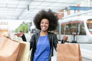 Young woman with afro hair at city train station holding up shopping bags, portraitの写真素材 [FYI03622580]