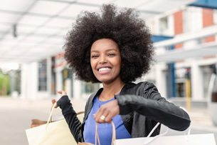 Young woman with afro hair at city train station holding up shopping bags, portraitの写真素材 [FYI03622582]