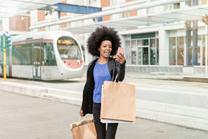 Young woman with afro hair at city train station carrying shopping bags, taking smartphone selfieの写真素材 [FYI03622586]