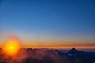 Sun glowing on horizon over mountain range, Saas-Fee, Valais, Switzerlandの写真素材 [FYI03622752]