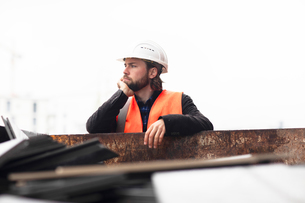Mid adult male construction worker leaning against waste skip contemplatingの写真素材 [FYI03622784]