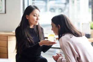 Woman smelling glass of lemon juice held by friendの写真素材 [FYI03622798]