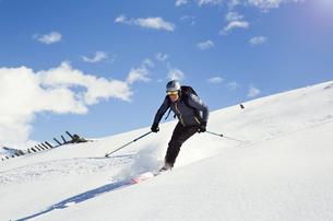 Mature man skiing down snow covered mountain,  Styria, Tyrol, Austriaの写真素材 [FYI03622897]
