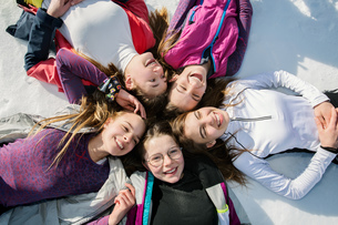 Five teenage girl skiers lying in a circle in snow, overhead view, Tyrol, Styria, Austriaの写真素材 [FYI03622922]