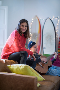 Young woman sitting up on living room sofa with young man playing guitarの写真素材 [FYI03622936]