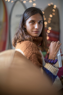 Young woman in knit sweater relaxing on living room sofa looking over her shoulder, portraitの写真素材 [FYI03622944]