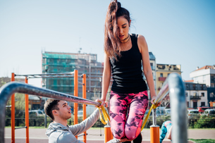 Calisthenics class at outdoor gym, male trainer encouraging young woman on parallel barsの写真素材 [FYI03622951]