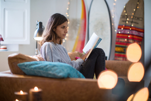 Young woman sitting on living room sofa reading a bookの写真素材 [FYI03622952]