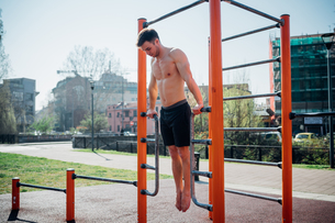 Calisthenics at outdoor gym, bare chested young man doing backward push ups on exercise equipmentの写真素材 [FYI03622963]