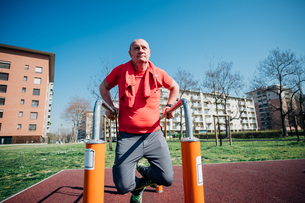 Calisthenics class at outdoor gym, mature man doing push ups on parallel barsの写真素材 [FYI03622973]