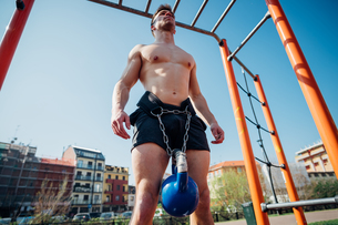 Calisthenics at outdoor gym, bare chested young man standing with kettlebell on waist harnessの写真素材 [FYI03622974]
